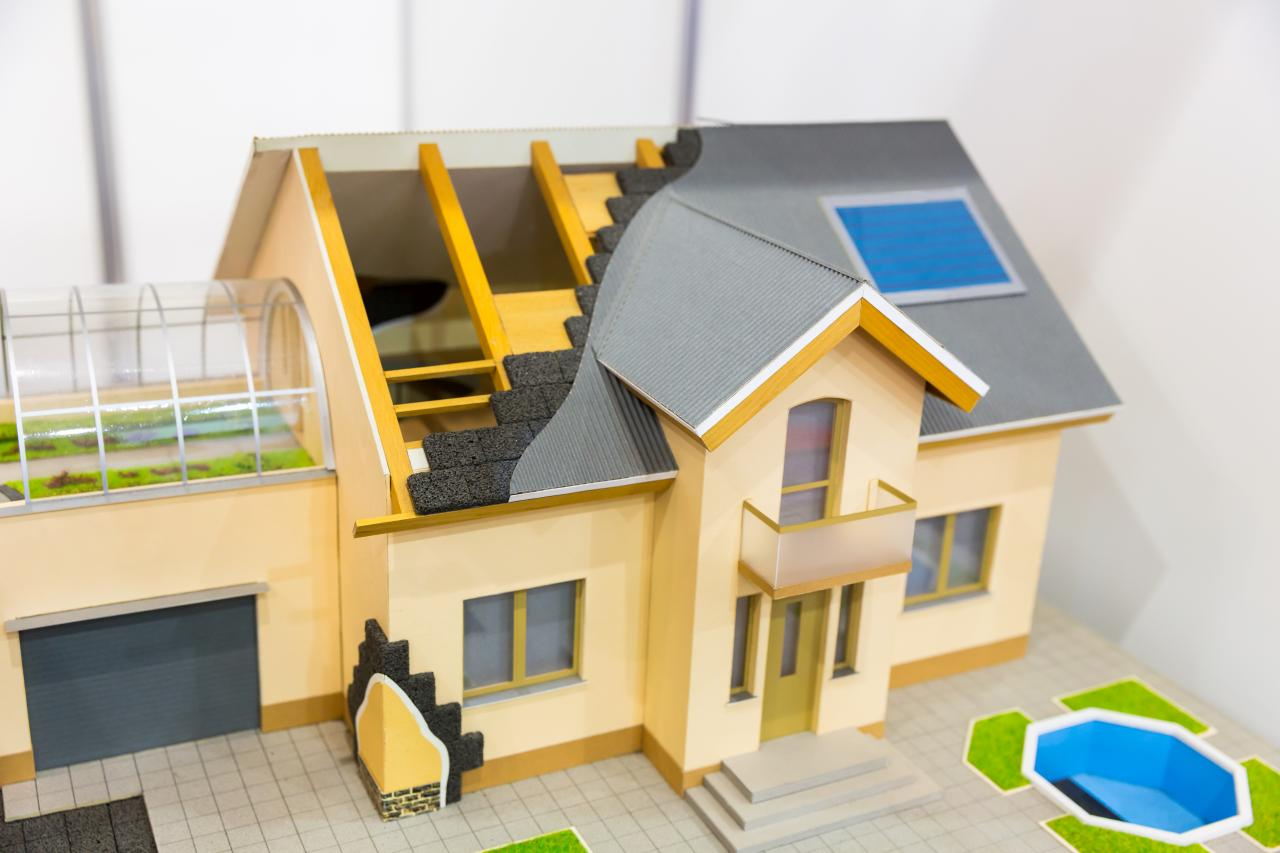 Model of house, thermal insulation of roof concept. Energy and money saving materials and systems